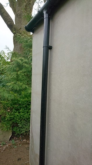 Garden room's black PVC guttering and a downpipe connected to a local soakaway