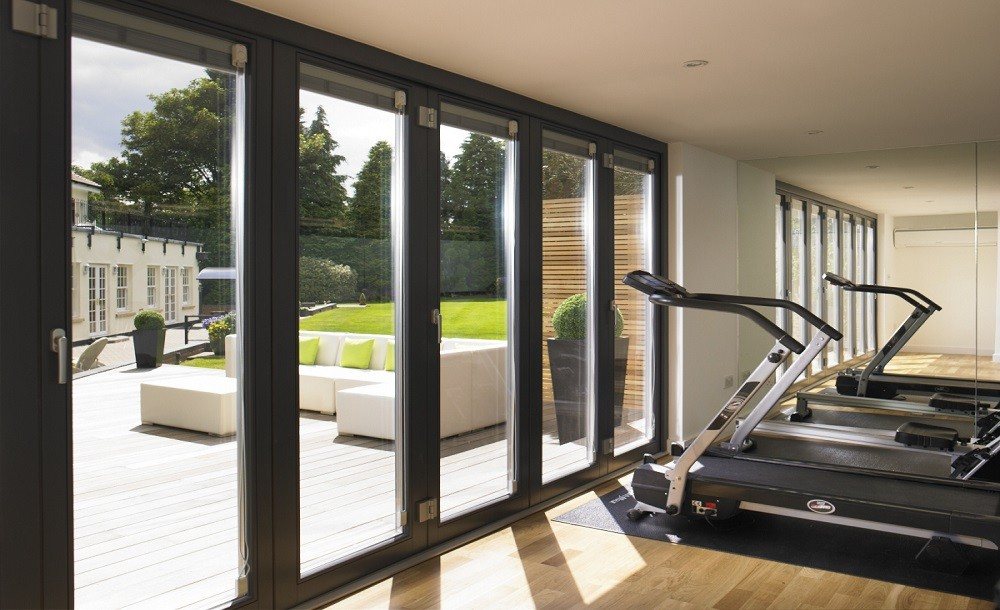 Bifolding double glazed doors for a garden gym by Rooms Outdoor